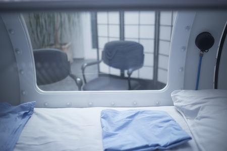 병원 클리닉의 부상을위한 전문적인 치료를 위해 사용되는 고주파 산소 요법 (HBOX) 챔버 탱크. 외관보기 창 및 내부 반사 베개와 침대.
