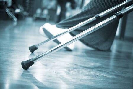 Aluminium metal crutches on floor in hospital clinic waiting room with legs defocused behind. photo