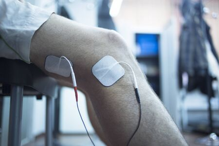 Patient knee, leg, thigh and calf in physiotherapy electrical impulse stimulation rehabiliation treatment from injury in hospital clinic with electrical stimulus attached with plaster.
