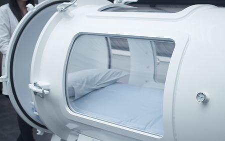 Hyperbaric Oxygen Therapy (HBOT) chamber tank used for specialised medical treatment for injuries in hospital clinic. Exterior viewing window and reflection with pillow and bed inside. Foto de archivo