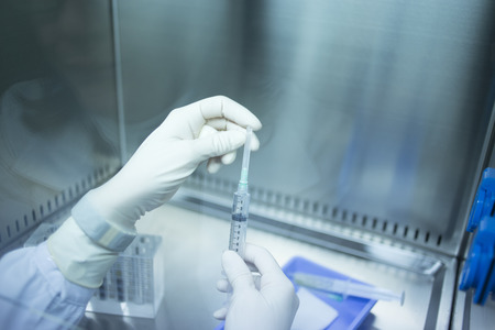 Hands of medical laboratory technician wearing white sterile gloves preparing PRP platelet rich plasma from blood human growth factors in hospital clinic for orthopedic surgery and Traumatology rehabilitation treatment with syringe injection and test tube Banco de Imagens