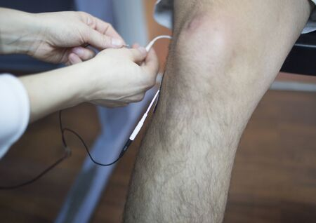 leg calf injury: Patient knee, leg, thigh and calf in physiotherapy electrical impulse stimulation rehabiliation treatment from injury in hospital clinic with electrical stimulus attached with plaster.