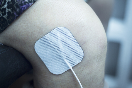 leg calf injury: Old lady patient knee, leg, thigh and calf in electrical stimulus physiotherapy rehabiliation treatment from injury in hospital clinic with electrical stimulus attached with plaster. Stock Photo