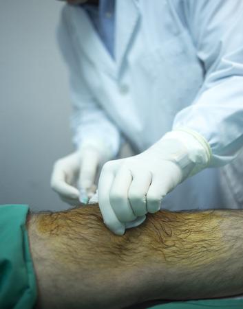 inyeccion: Hombre Traumatolog�a y Ortopedia m�dico cirujano inyectar paciente en la cama de hospital en la rodilla en la cl�nica privada con PRP plasma rico en plaquetas Crecimiento Factores Humanos C�lulas madre para tratar el desperdicio cart�lago lesi�n articular y el dolor.