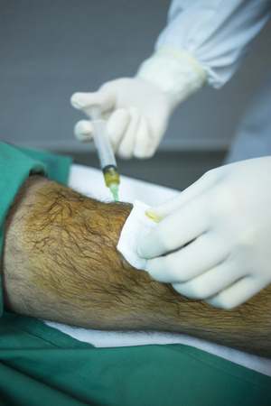 Male Traumatology and Orthopedics surgeon doctor injecting patient on hospital bed in knee in private clinic with PRP Platelet Rich PLasma Human Growth Factors Stem Cells to treat cartilage wastage joint injury and pain.