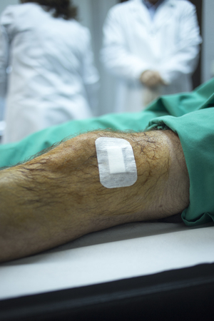 human factors: Male Traumatology and Orthopedics surgeon doctor injecting patient on hospital bed in knee in private clinic with PRP Platelet Rich PLasma Human Growth Factors Stem Cells to treat cartilage wastage joint injury and pain.
