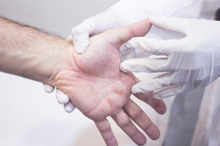 orthopedics: Hombre ortopedia Traumatologist cirujano m�dico examinando a hombre de mediana edad del paciente para determinar la lesi�n, el dolor, la movilidad y para diagnosticar el tratamiento m�dico en los dedos de la mano y la mu�eca. Foto de archivo