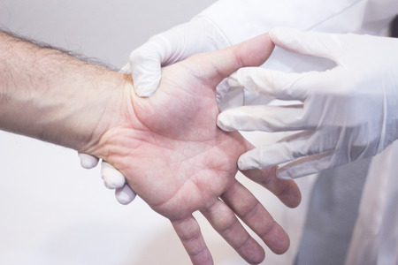 Male Traumatologist orthopedics surgeon doctor examining middle aged man patient to determine injury, pain, mobility and to diagnose medical treatment in hand fingers and wrist. Stock Photo