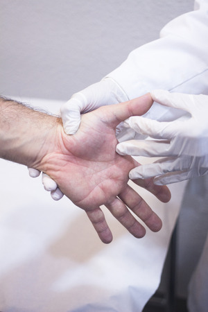 orthopedic: Male Traumatologist orthopedics surgeon doctor examining middle aged man patient to determine injury, pain, mobility and to diagnose medical treatment in hand fingers and wrist. Stock Photo