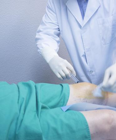 Traumatologie et Orthopédie Homme chirurgien médecin injectant du patient sur un lit d'hôpital dans le genou dans une clinique privée avec PRP plasma riche en plaquettes croissance Facteurs humains des cellules souches pour traiter le cartilage le gaspillage des blessures et des douleurs articulaires. Banque d'images - 39363917