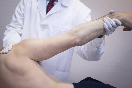 cirujano: Hombre ortopedia Traumatologist cirujano m�dico examinando a hombre de mediana edad del paciente para determinar la lesi�n, el dolor, la movilidad y para diagnosticar el tratamiento m�dico en el hombro, el brazo, el codo y la mu�eca.