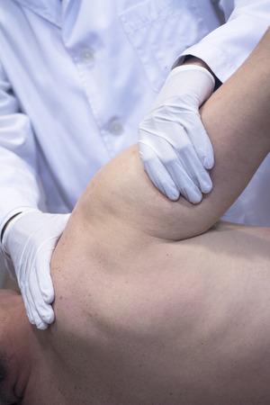 orthop�die: Homme traumatologue orthop�die chirurgien m�decin examinateur homme d'�ge des patients milieu pour d�terminer blessure, la douleur, la mobilit� et de diagnostiquer un traitement m�dical dans l'�paule, le bras, le coude et le poignet. Banque d'images