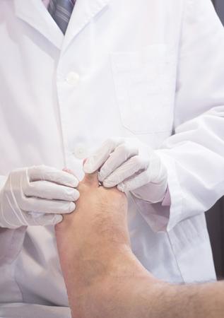 orthopedics: Hombre ortopedia Traumatologist cirujano m�dico examinando a hombre de mediana edad del paciente para determinar la lesi�n, el dolor, la movilidad y para diagnosticar el tratamiento m�dico para el pie, el tobillo, la pierna y pantorrilla.