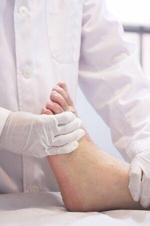orthop�die: Homme traumatologue orthop�die chirurgien m�decin examinateur homme d'�ge des patients milieu pour d�terminer blessure, la douleur, la mobilit� et de diagnostiquer un traitement m�dical pour pied, cheville, jambe et mollet.