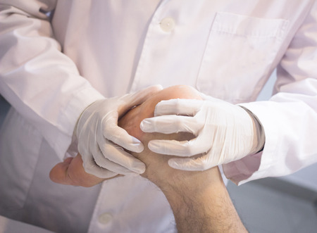 Male Traumatologist orthopedics surgeon doctor examining middle aged man patient to determine injury, pain, mobility and to diagnose medical treatment for foot, ankle, leg and calf.