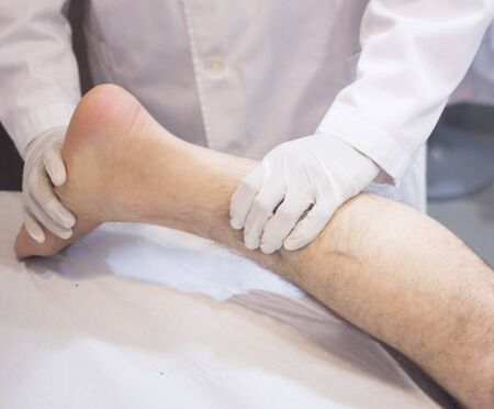 calf pain: Male Traumatologist orthopedics surgeon doctor examining middle aged man patient to determine injury, pain, mobility and to diagnose medical treatment for foot, ankle, leg and calf.
