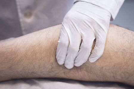 leg calf injury: Male Traumatologist orthopedics surgeon doctor examining middle aged man patient to determine injury, pain, mobility and to diagnose medical treatment for foot, ankle, leg and calf.