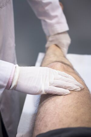 Male Traumatologist orthopedics surgeon doctor examining middle aged man patient to determine injury, pain, mobility and to diagnose medical treatment in knee meniscus cartilage injury. photo