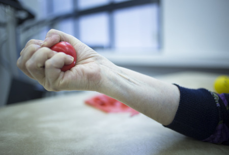 stimulation: Hand stimulation used to treat pain, muscles injuries, strains and tension in hospital physiotherapy medical rehabilitation clinic for patient using rubber ball exercises.