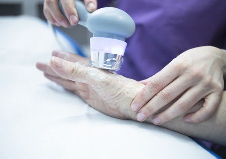 stimulator: Electro stimulation used to treat pain, muscles injuries, strains and tension in hospital physiotherapy medical rehabilitation clinic for patient hand.