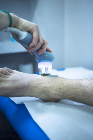 stimulator: Electro stimulation used to treat pain, muscles injuries, strains and tension in hospital physiotherapy medical rehabilitation clinic for patient foot, heel and ankle. Stock Photo