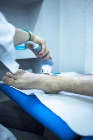 stimulation: Electro stimulation used to treat pain, muscles injuries, strains and tension in hospital physiotherapy medical rehabilitation clinic for patient foot, heel and ankle. Stock Photo