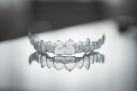 braces: Invisible Invisalign plastic dental teeth brackets tooth braces isolated with shallow depth of focus artistic photograph. Stock Photo