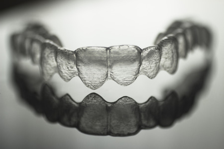 invisible: Invisible Invisalign plastic dental teeth brackets tooth braces isolated with shallow depth of focus artistic photograph. Stock Photo