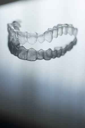 Invisible Invisalign plastic dental teeth brackets tooth braces isolated with shallow depth of focus artistic photograph. Stock Photo