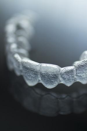 보이지 않는 Invisalign 플라스틱 치과 치아 브라켓 치아 초점 예술 사진의 얕은 깊이와 격리 된 중괄호. 스톡 콘텐츠