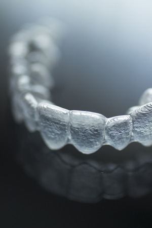 Invisible Invisalign plastic dental teeth brackets tooth braces isolated with shallow depth of focus artistic photograph. Standard-Bild