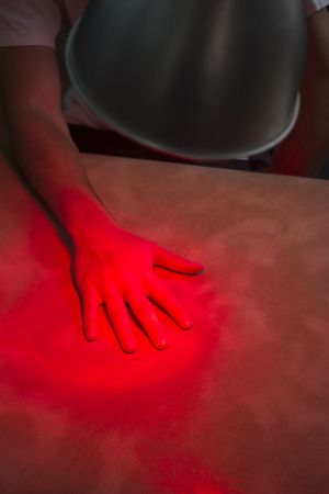forearm: Hand, fingers, forearm and arm of injured patient receiving treamente under red physiotherapy rehabilitation hospital clinic heat therapy lamp.