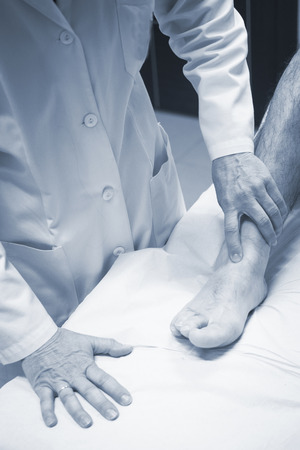 meniscus: Traumatologist orthopedic surgeon doctor examining middle aged man patient to determine injury, pain, mobility and to diagnose medical treatment in leg, knee meniscus cartilage, ankle and foot injury. Stock Photo