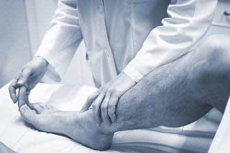 foot doctor: Traumatologist orthopedic surgeon doctor examining middle aged man patient to determine injury, pain, mobility and to diagnose medical treatment in leg, knee meniscus cartilage, ankle and foot injury. Stock Photo