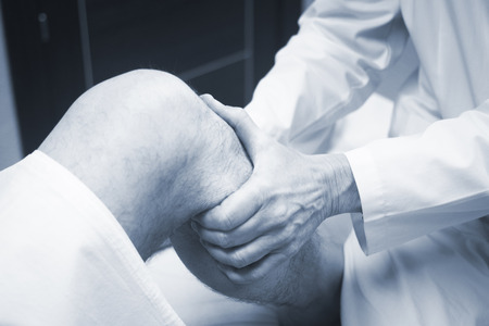 Traumatologist orthopedic surgeon doctor examining middle aged man patient to determine injury, pain, mobility and to diagnose medical treatment in leg, knee meniscus cartilage, ankle and foot injury. Standard-Bild
