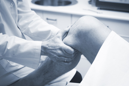 Traumatologist orthopedic surgeon doctor examining middle aged man patient to determine injury, pain, mobility and to diagnose medical treatment in leg, knee meniscus cartilage, ankle and foot injury. Stockfoto