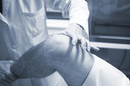 cirujano: Traumat�logo cirujano ortop�dico m�dico examinando hombre de mediana edad paciente para determinar la lesi�n, el dolor, la movilidad y para el diagn�stico de tratamiento m�dico en la pierna, la rodilla menisco cart�lago, tobillo y lesi�n en el pie.