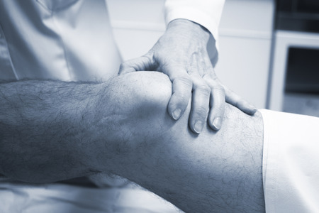 Traumatologist orthopedic surgeon doctor examining middle aged man patient to determine injury, pain, mobility and to diagnose medical treatment in leg, knee meniscus cartilage, ankle and foot injury. Stock Photo