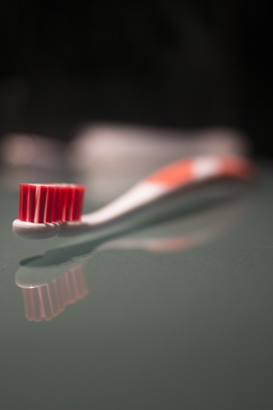 color photo: Toothbrush by wash basin at night still life color photo.