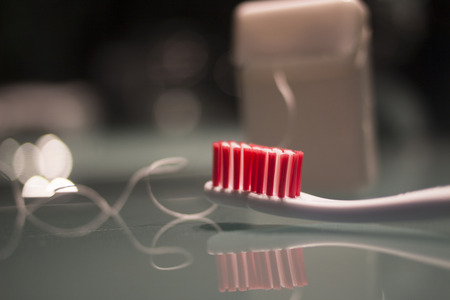 waxed: Toothbrush and dental hygiene waxed tape mint floss by wash basin at night still life color photo. Stock Photo