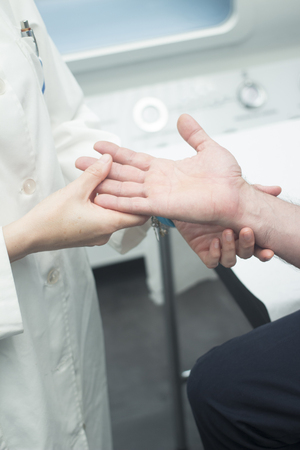 female elbow: Female Traumatologist orthopedic surgeon doctor examining middle aged man patient to determine injury, pain, mobility and to diagnose medical treatment in shoulder, arm, elbow, wrist and fingers.