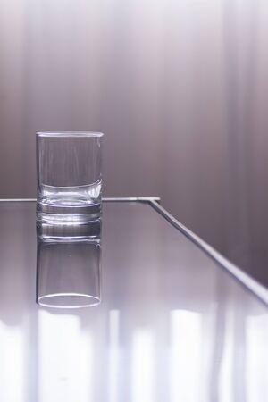 window light: Glass of water on table in window light effect photo.