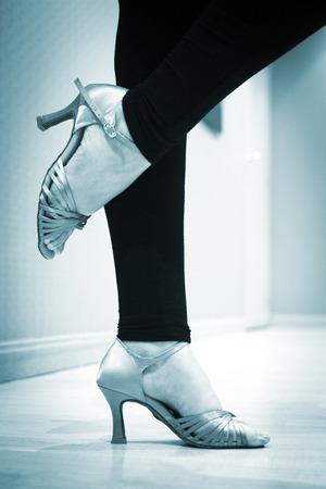 tangoing: Dancing shoes feet and legs of female ballroom and latin salsa dancer dance teacher in dance school rehearsal room class. Stock Photo