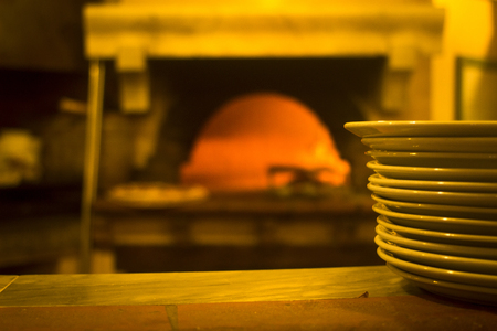 wood and fire: Italian pizzeria traditinal wood fire oven pizza and stack of plates in restaurant in Rome Italy. Stock Photo