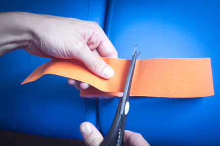 color therapist: Physiotape physiotherapy color tape bandage for taping treatment in real life hospital clinic being applied by physiotherapist cutting the tape with scissors.