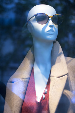 shop window: Shop dummy fashion mannequin in store boutique shop window wearing dark sunglasses artistic photo.