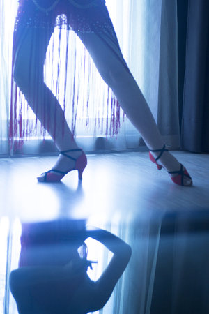 milonga: Dancing shoes feet and legs of female ballroom and latin salsa dancer dance teacher in dance school rehearsal room class. Stock Photo