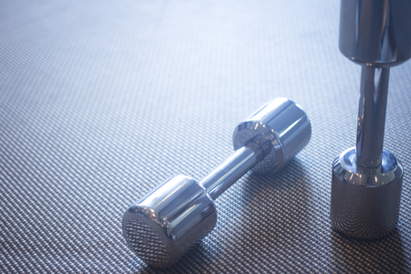 health club: Dumbbell gym metal weights in exercise room in sports bodybuilder gym health club fitness studio for bodybuilding and weight training. Stock Photo