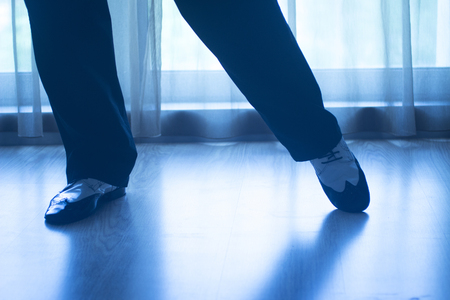 waltzing: Dancing shoes feet and legs of male ballroom and latin salsa dancer dance teacher in dance school rehearsal room class.
