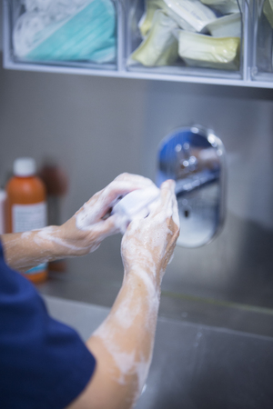 scrubbing: Traumatology orthopedic surgery hospital emergency operating room prepared for arthroscopy operation photo of nurse scrubbing doctor washing hands sterilising with sterilisation soap and products.